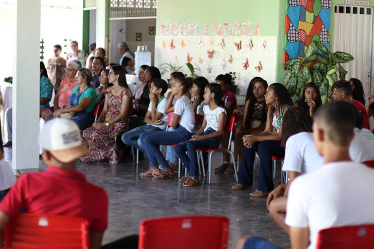 Estudantes sentados em cadeiras no pátio da escola, assistindo à palestra